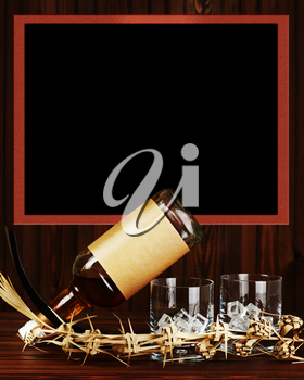Two glasses with ice for whiskey and bottle on dark wooden background.