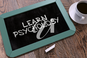 Handwritten Learn Psychology on a Blue Chalkboard. Top View Composition with Chalkboard and White Cup of Coffee. 3D Render.