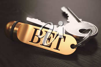 Keys and Golden Keyring with the Word Bet over Black Wooden Table with Blur Effect. Toned Image.