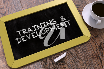 Hand Drawn Training and Development Concept  on Small Yellow Chalkboard. Business Background. Top View.
