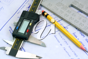 Royalty Free Photo of a Digital Calliper and Blueprints