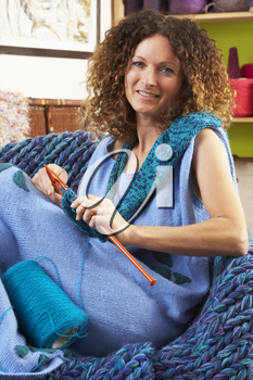 Close Up Of Woman Sitting In Chair Knitting