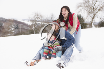 Family In Snow Riding On Sledge