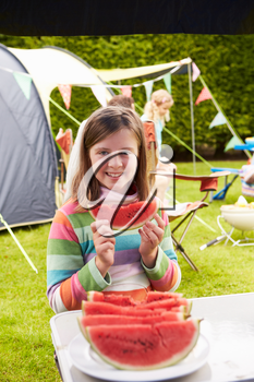 Girl Eating Watermelon Whilst On Family Camping Holiday