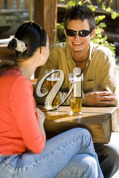 A young couple enjoying a glass pf beer with each other