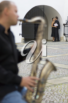 A street musician playing his saxophone serenades two young lovers