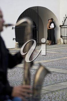 A street musician playing a saxophone serenades a romantic couple as the woman looks on thoughtfully