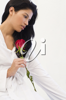 Studio shot of a beautiful young Latina woman dressed in a white robe, looking thoughtful and holding a rose