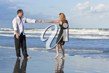 A young man and woman holding hands and having fun dancing as a romantic couple on a beach with a bright blue sky and sea