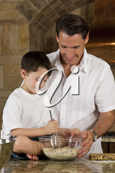 An attractive smiling father and son cooking baking chocolate chip cookies in a kitchen at home