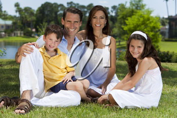 An attractive happy, smiling family of mother, father, son and daughter sitting on grass outside in warm summer sunshine