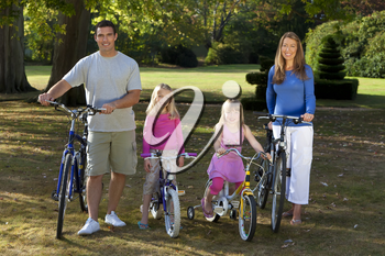 A young family with mother father and two blond daughters riding their bikes in a sun bathed green park