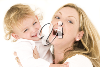 A young blonde mother and her son dressed in white and having laughing together