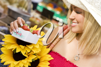 A beautiful young woman shopping for strawberries in a market
