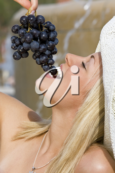 A beautiful young blond woman sitting in front of a fountain eating a bunch of black grapes
