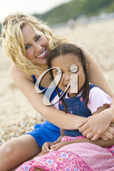 A beautiful blond haired blue eyed young woman having fun with a mixed race young girl at the beach