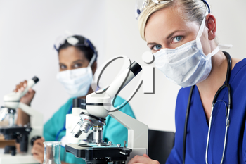 A blond female medical or scientific researcher or doctor using her microscope in a laboratory with her Asian colleague out of focus behind her.