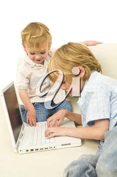 Two young children using a laptop while sitting on a settee