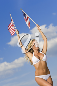 A stunningly beautiful young woman in a white bikini holds two stars and stripes flags above her head