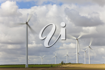 A farm of wind turbines or windmills providing alternative sustainable green energy, situated in a field of sunflowers