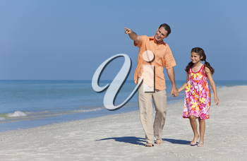 A happy father and child, his daughter, walking holding hands and pointing on a sunny beach