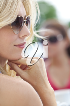 Portrait of naturally beautiful woman in her twenties with blond hair wearing heart shaped sunglasses, shot outside in natural sunlight