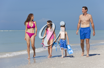 A happy family of mother, father and two children, son and daughter, in swimming costumes having fun in the sea on a sunny beach