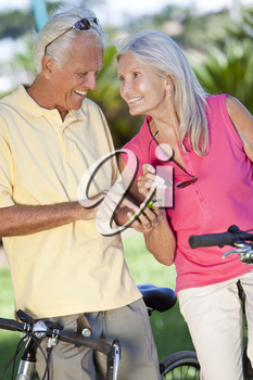 Happy senior man and woman couple cycling and together using a smart phone outside in sunshine