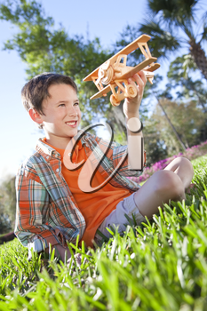A young boy outside sitting on the grass playing with his toy model airplane