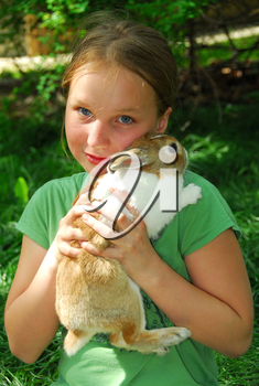 Portrait of a young girl holding a bunny outside