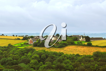 Scenic view on agricultural landscape with a farm house in rural Brittany, France