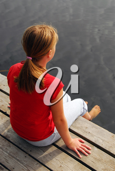 Young girl dipping feet in the lake from a wooden boat dock