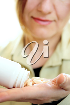 Mature woman with pills or vitamins on her hand