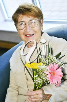 Elderly woman with glasses holding flowers and smiling