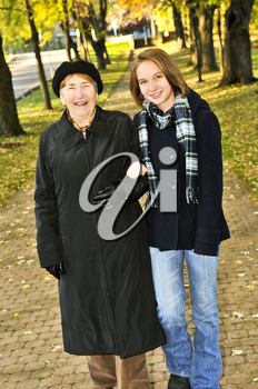 Teen granddaughter walking with grandmother in autumn park