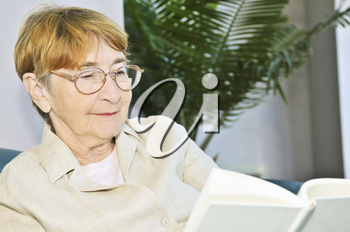 Elderly woman relaxing on couch reading a book