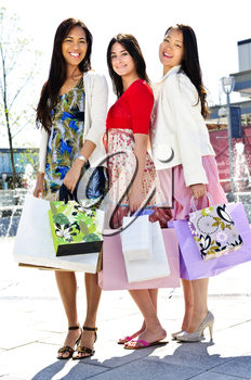 Group of young girl friends holding shopping bags at mall