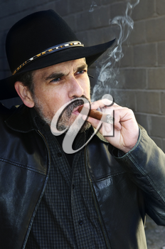 Man with beard in cowboy hat smoking cigar