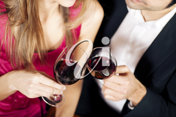 Young couple - man and woman - in a restaurant clinking the red wine glasses; focus on the glasses