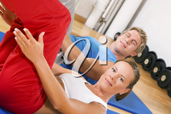 Couple with brightly colored clothes doing sit-ups in the gym