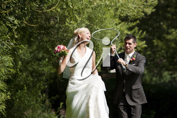 Happy wedding couple, the groom is catching his bride with a dip net in a rather playful way