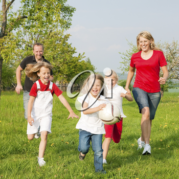 Happy family playing football, one child has grabbed the ball and is being chased by the others