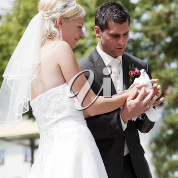 Happy wedding couple, they are holding doves in their hands and want to let them fly free as a symbol of love