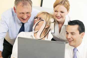Team of four business people working in front a computer looking at the screen, seeing something good obviously