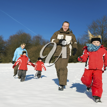 Active Family in winter running down a hill in the snow