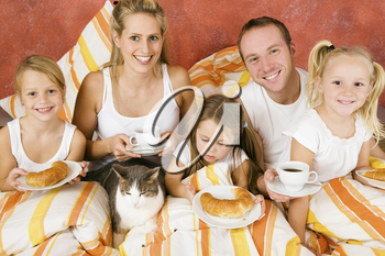 Family of five and their cat having breakfast in their bed in the morning