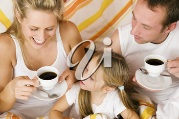 Family having breakfast in their bed in the morning