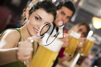 Group of three friends in a bar drinking beer - selective focus on beautiful woman in front pointing her glass at the viewer