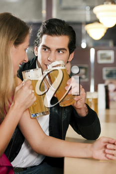 Group of people in a bar or restaurant drinking beer, one couple flirting very obviously having a lot of fun