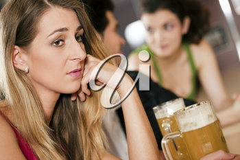Group of people in a bar or restaurant drinking beer, woman in front being sad since her boyfriend is flirting with another girl dumping her